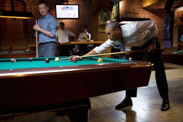President Barack Obama whistles along to the music as he shoots pool with Col